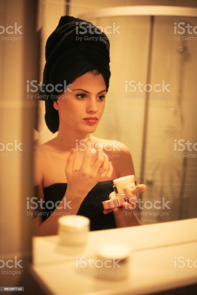 Young woman applying cream in bathroom. Portrait of beautiful woman applying anti-wrinkles cream. stock photo