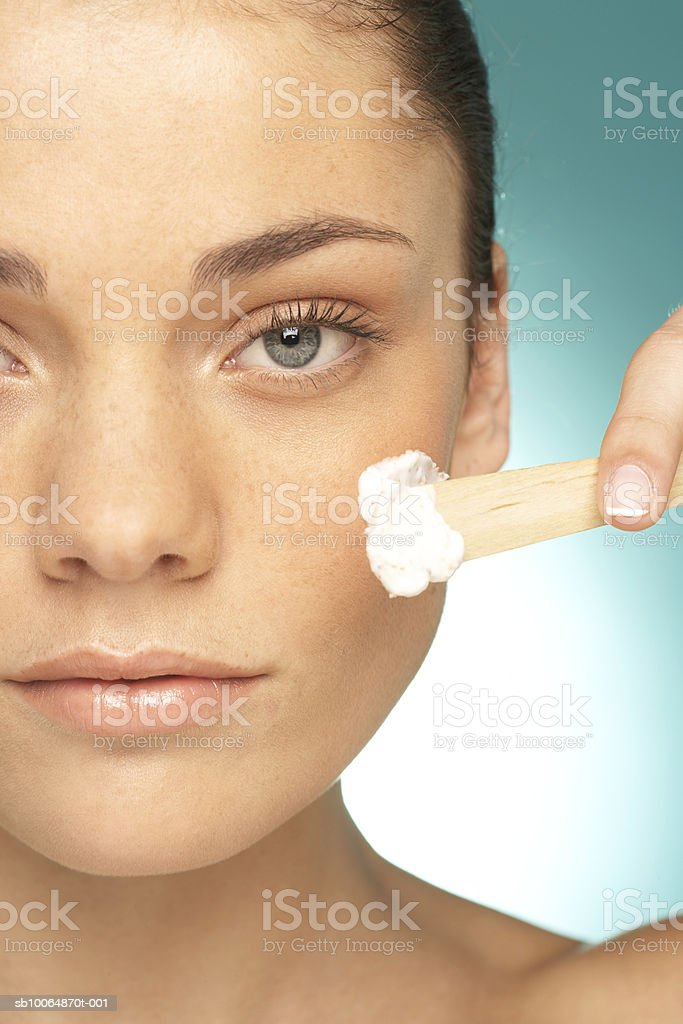 Young woman applying cream on cheek, portrait, close-up royalty free stockfoto