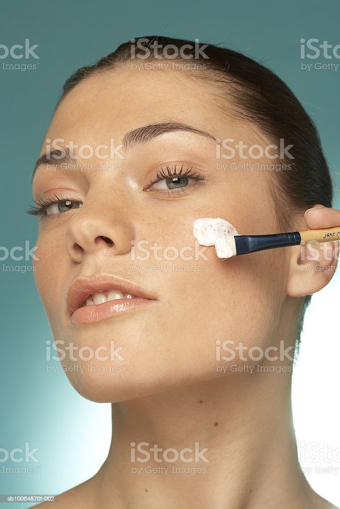 Young woman applying cream on cheek, portrait, close-up foto de stock libre de derechos