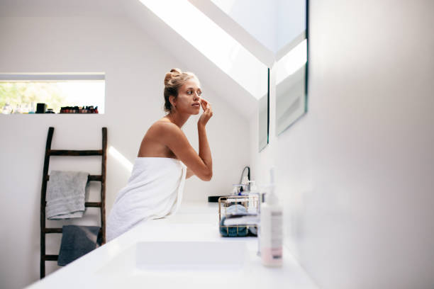 Young woman applying cream on her face in bathroom stock photo