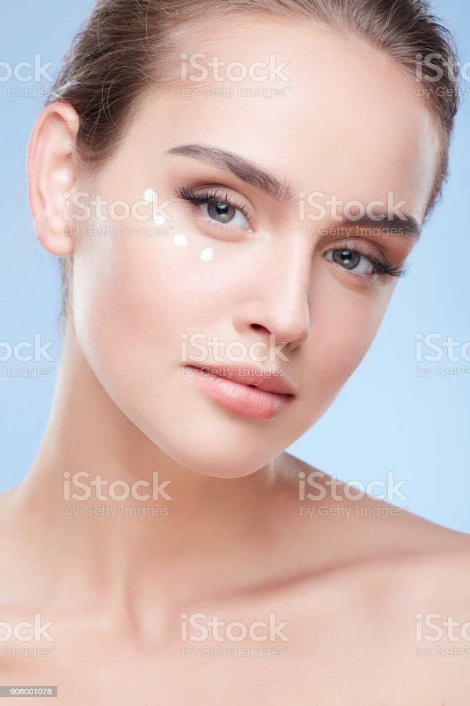 Young woman applying cream under eyes stock photo