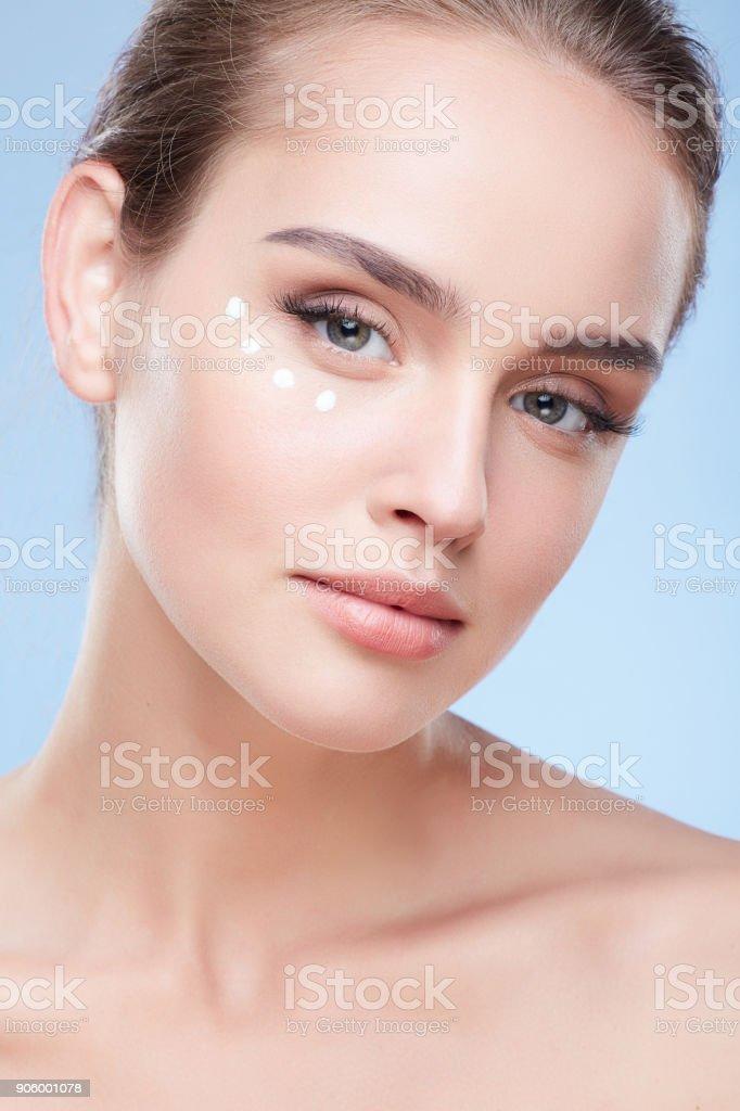Junge Frau auftragen Creme unter den Augen – Foto