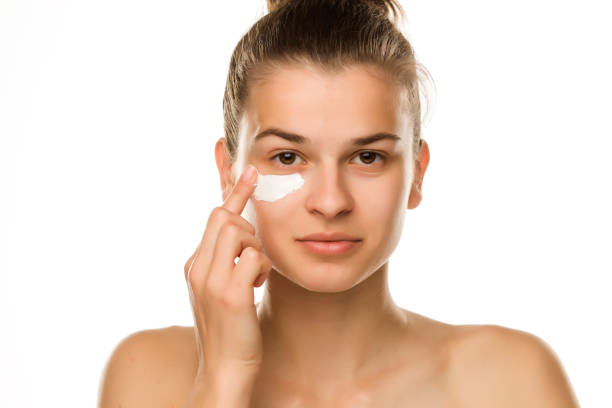 A young woman applying cream under her eyes on white background stock photo