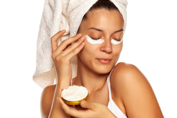 Young woman applying face cream under heer eyes on white background stock photo