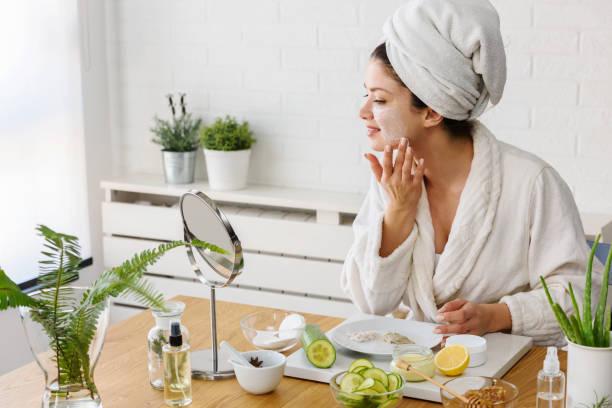 Junge Frau auftragen Gesichtsmaske zu Hause. Natürliche Hautpflege Routine für glühende Haut. – Foto