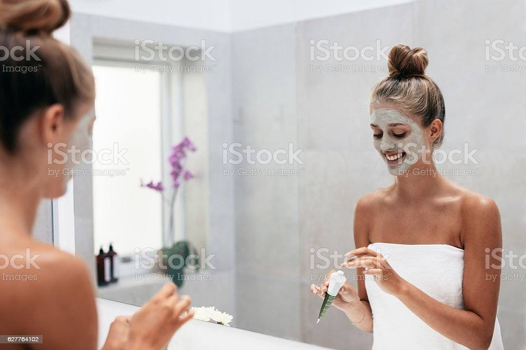 Young woman applying face mask in bathroom stock photo