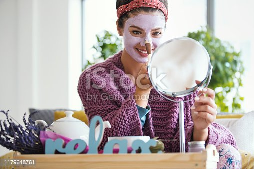Young woman applying facial mask. She's sitting on her bed looking at mirror and taking care of here skin during weekend morning.