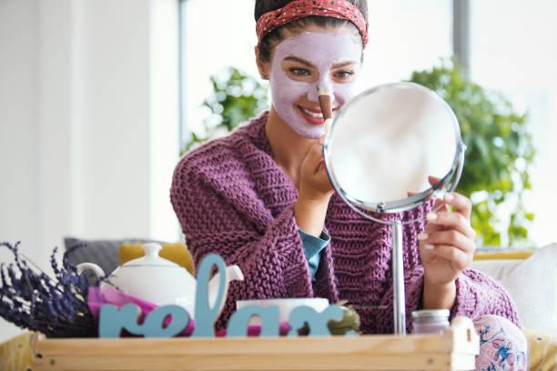 jonge vrouw die gezichtsmasker toepast. - mirror mask stockfoto's en -beelden
