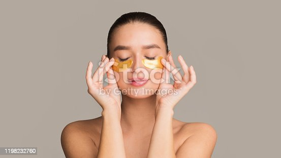 Young woman applying golden collagen patches under eyes, taking care of delicate skin around eyes
