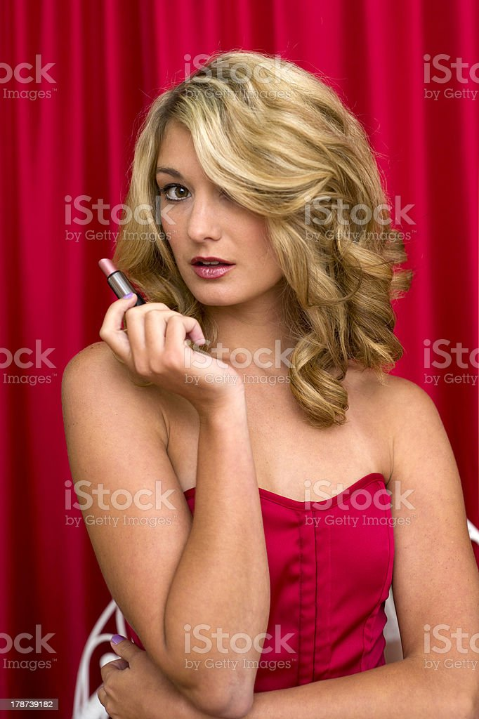 Young Woman Applying Lipstick in a Mirror royalty-free stock photo