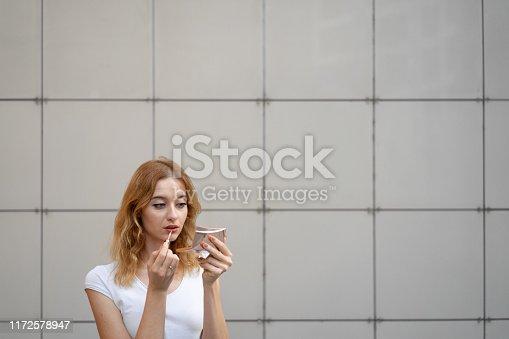 109721176istockphoto Young woman applying lipstick outdoors 1172578947