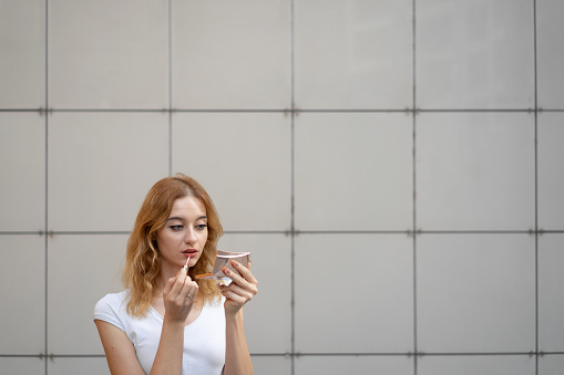 109721176 istock photo Young woman applying lipstick outdoors 1172578947