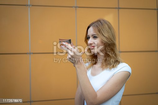 109721176istockphoto Young woman applying lipstick outdoors 1172578970