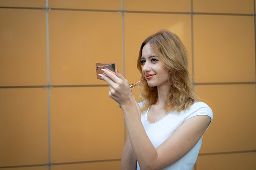 109721176 istock photo Young woman applying lipstick outdoors 1172578970