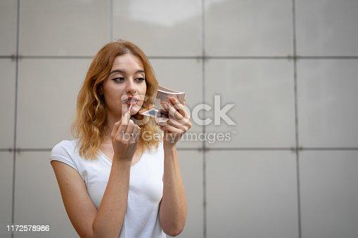 109721176istockphoto Young woman applying lipstick outdoors 1172578986
