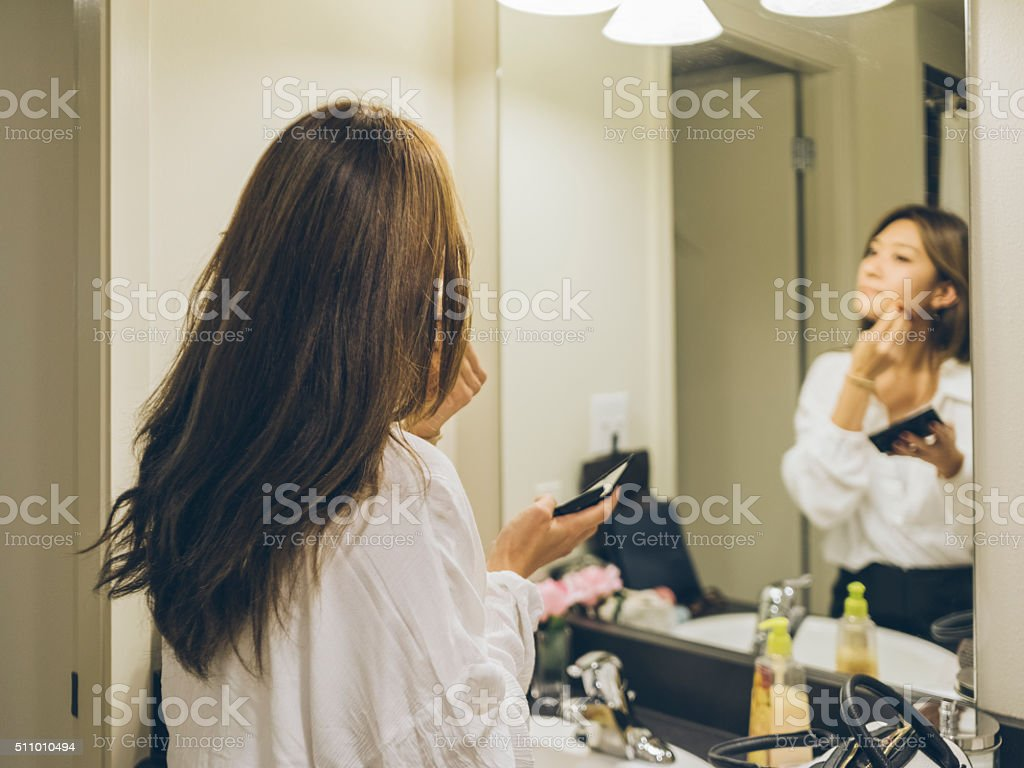 Young woman applying , looking in mirror stock photo