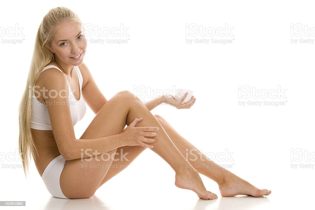 Young woman applying lotion to legs royalty-free stock photo
