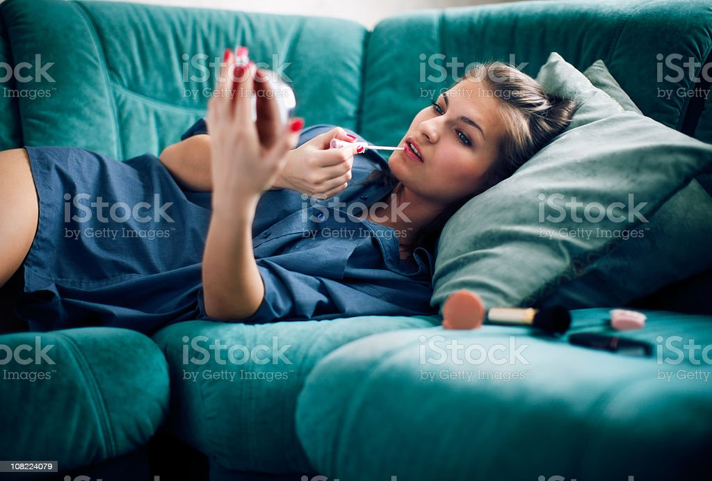 Young Woman Applying Make-Up and Lying on Couch stock photo
