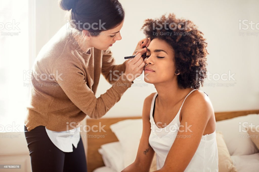 Young woman applying make-up for her friend stock photo