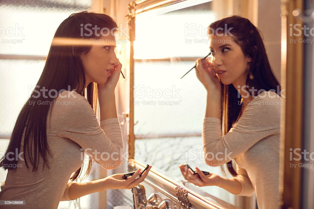 Young woman applying make-up in bathroom. stock photo