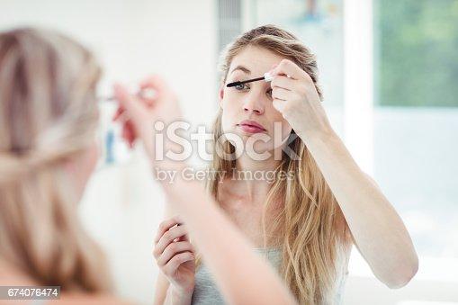 istock Young woman applying mascara 674076474