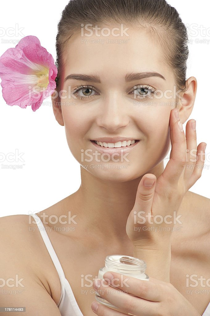 Young woman applying moisturizer cream stock photo