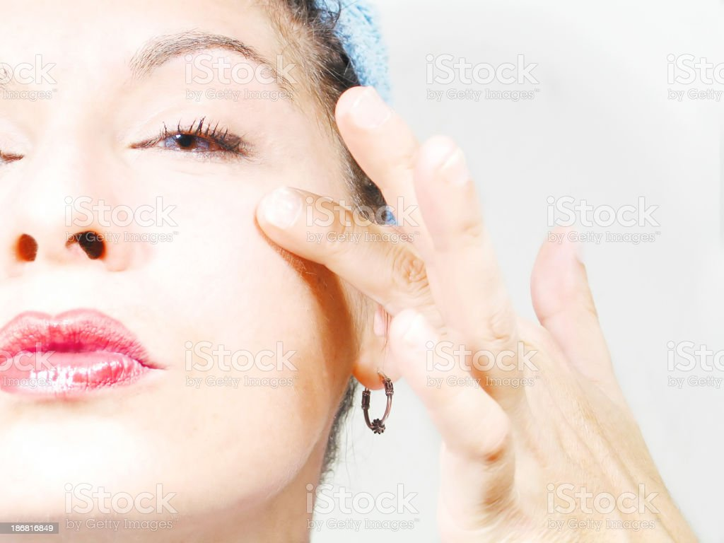 Young woman applying moisturizer royalty-free stock photo