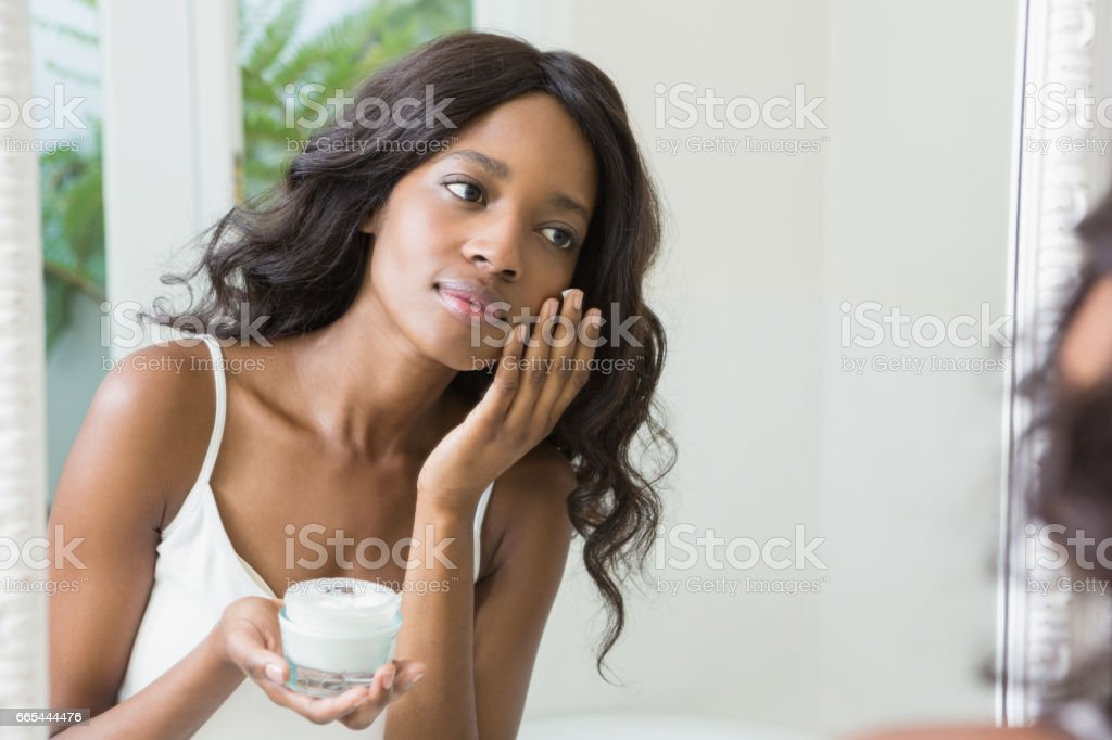 Jovem mulher aplicando hidratante - foto de acervo