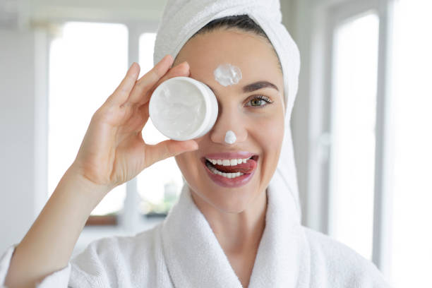 Young woman applying moisturizer to her skin at home stock photo