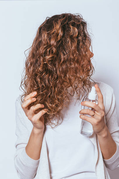 Young woman applying moisturizing spray to her curly hair stock photo