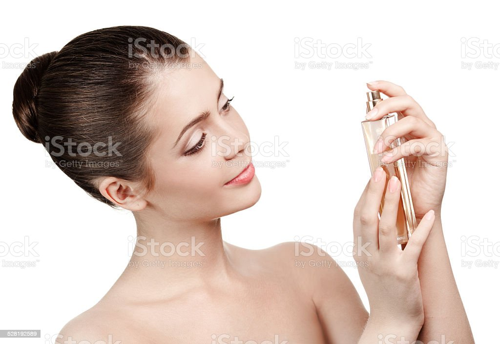 Young woman applying perfume on herself isolated stock photo