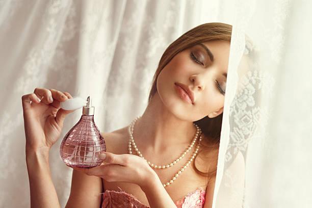 młoda kobieta stosowanie perfum - perfumowany zdjęcia i obrazy z banku zdjęć