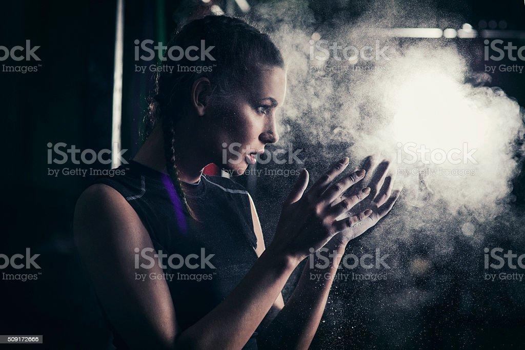 Mujer joven aplicar tiza en sus manos - foto de stock