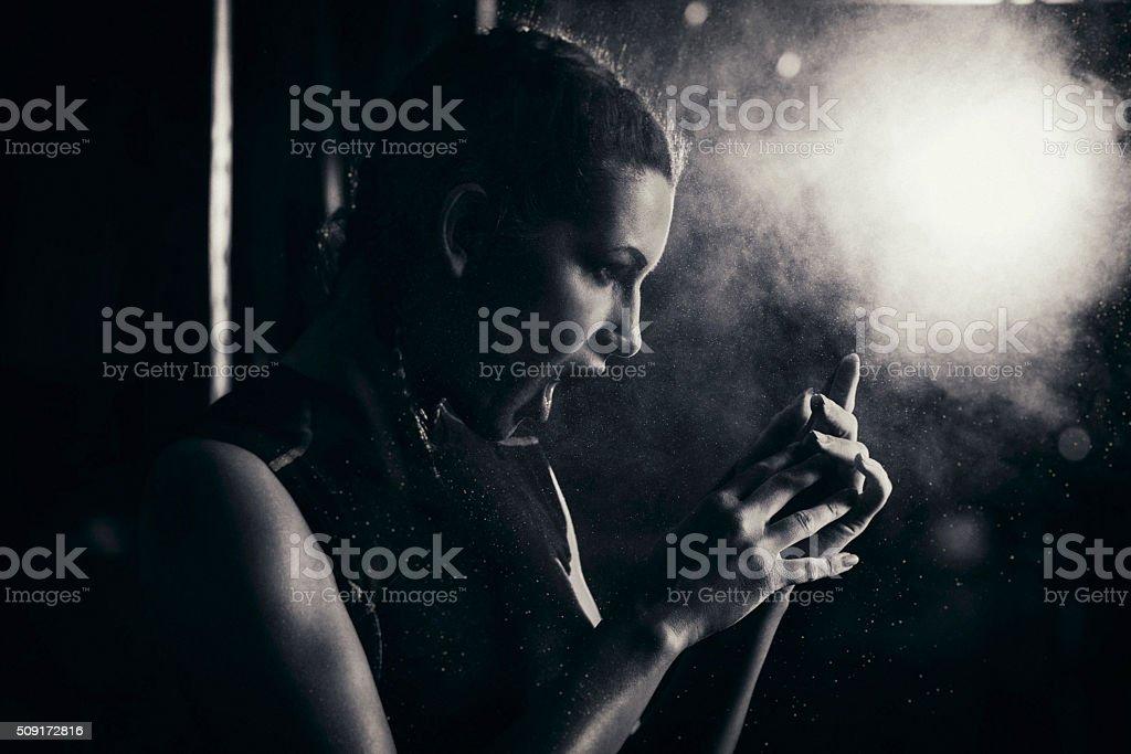 Young woman applying sports chalk on her hands stock photo