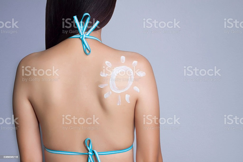 young woman applying sunscreen on her back stock photo