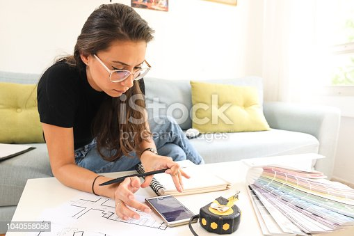 832105172 istock photo A young woman architect and an interior designer Drawing a plan 1040558058