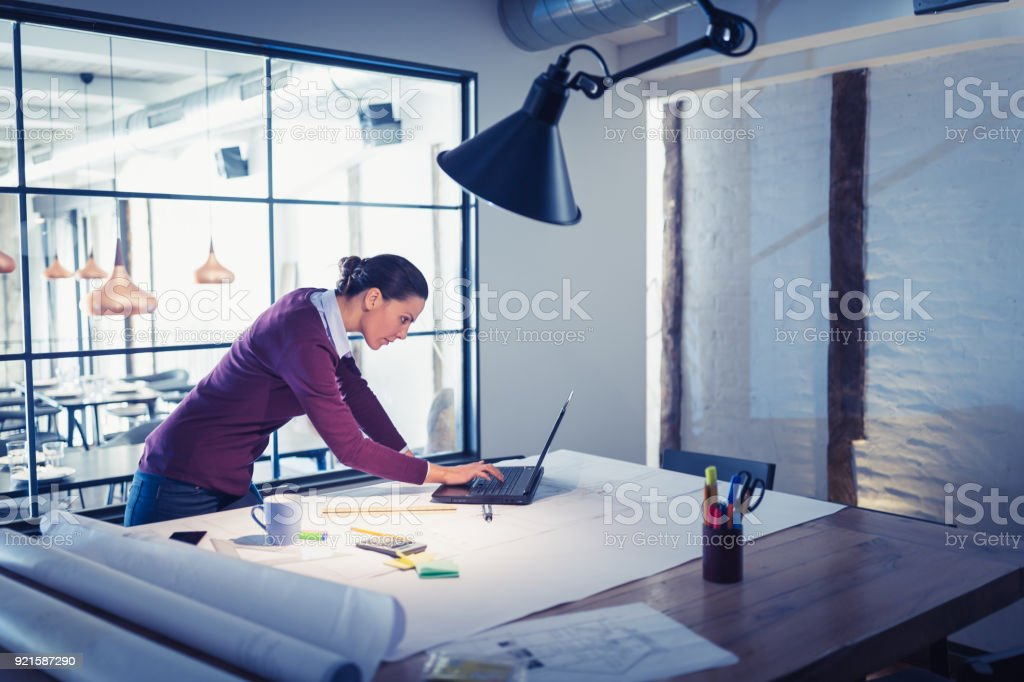 Young woman architect , working on a project. Modern architectural...