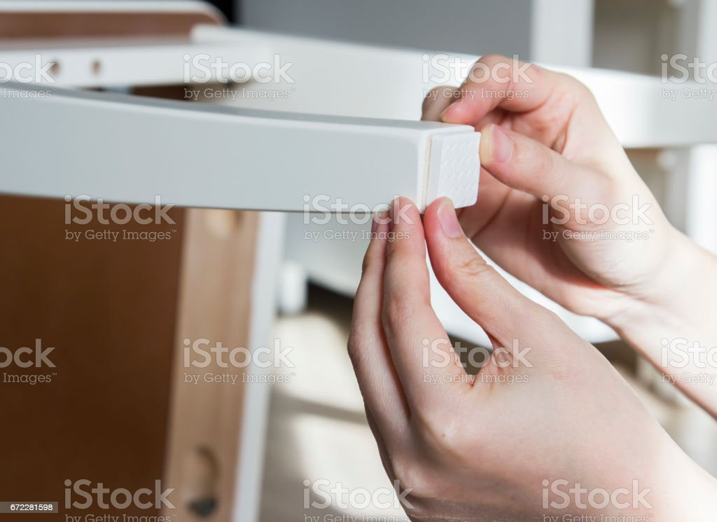 Young woman are sticking floor care pad at chair legs stock photo