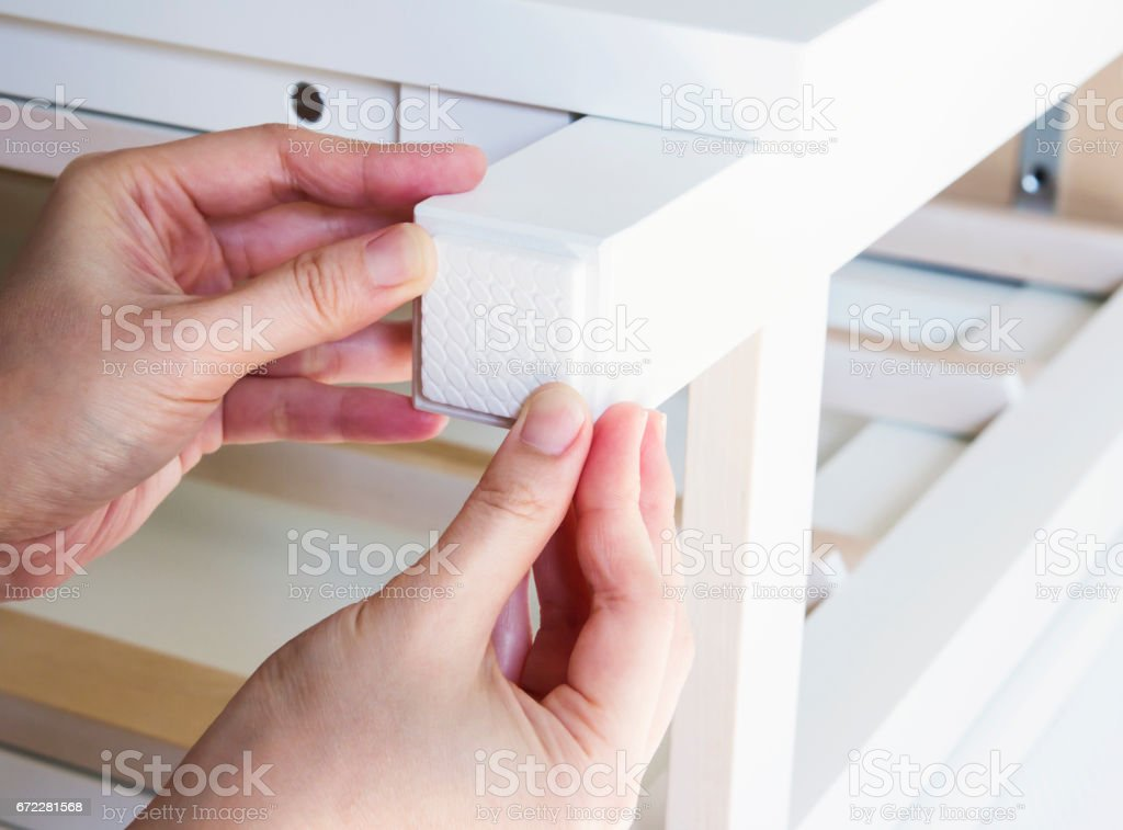 Young woman are sticking floor care pad at the table legs stock photo
