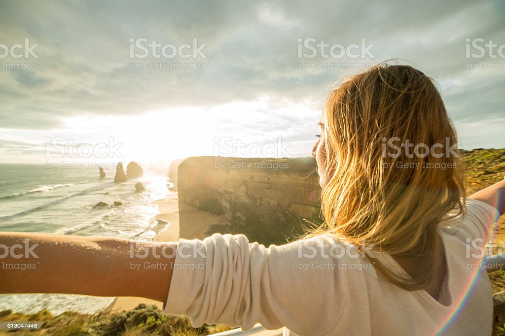 Young woman arms outstretched at sunset stock photo
