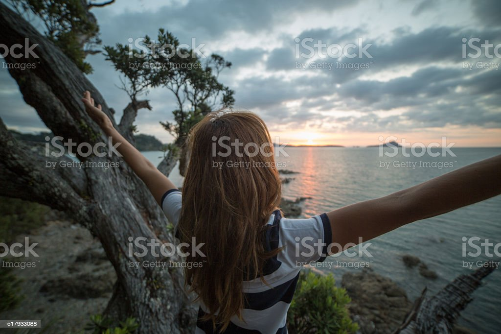 Young woman arms outstretched at the Coromandel Peninsula stock photo