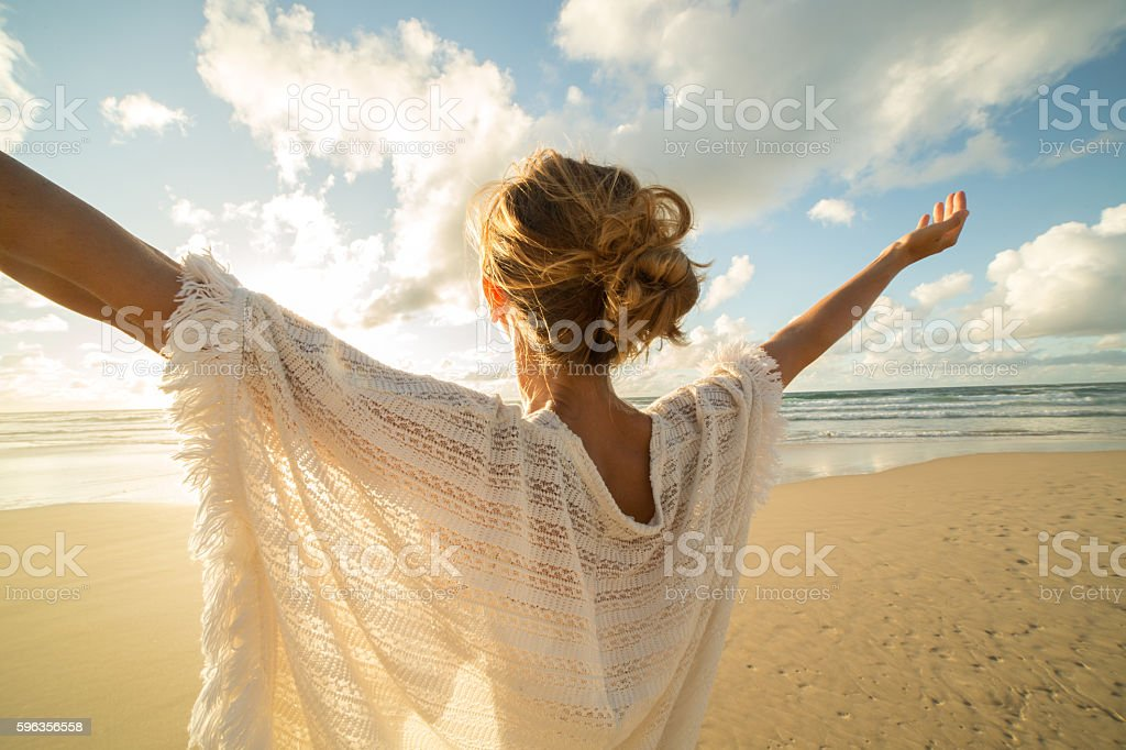 Young woman arms outstretched on the beach at sunset royalty-free stock photo