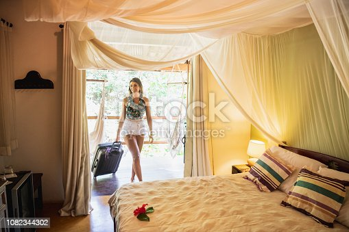 Woman in her 20s, pulling wheeled suitcase, entering luxury bedroom suite, with canopy over double bed