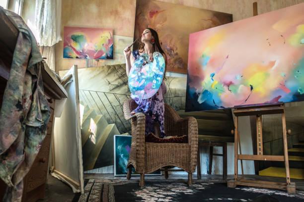 Junge Künstlerin, die Gemälde im viktorianischen Stil aufweist, ist im Studio – Foto