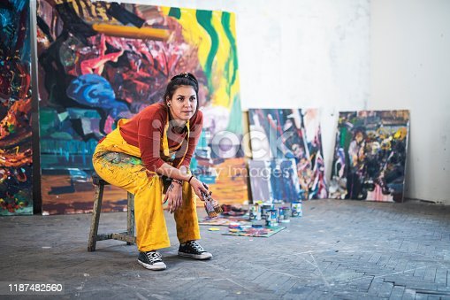 Full length portrait of young woman artist sitting in front of her big paintings in studio, she looking away.