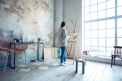 istock Young woman artist painting at home creative standing drawing 1143163619
