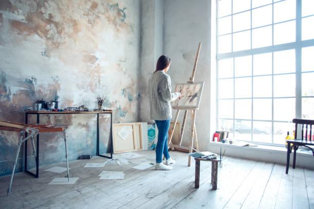 年輕女演出者繪畫在家創造性站立圖畫 - 藝術行業 個照片及圖片檔