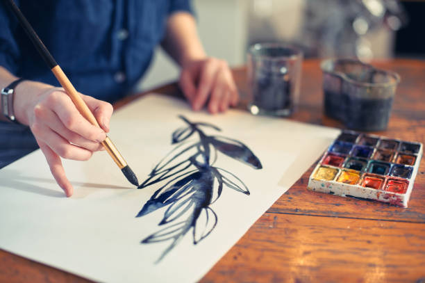 Young Woman Artist Working On Painting In Studio. Selective focus on foreground. stock photo