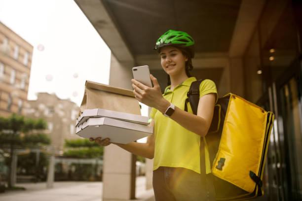 Junge Frau als Kurier liefert Pizza mit Gadgets – Foto