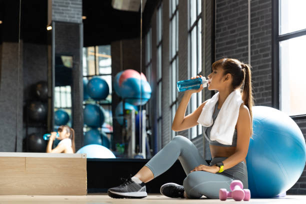Young woman asian drink water after workout In a room with a window with natural light. Fitness and healthy lifestyle concept stock photo